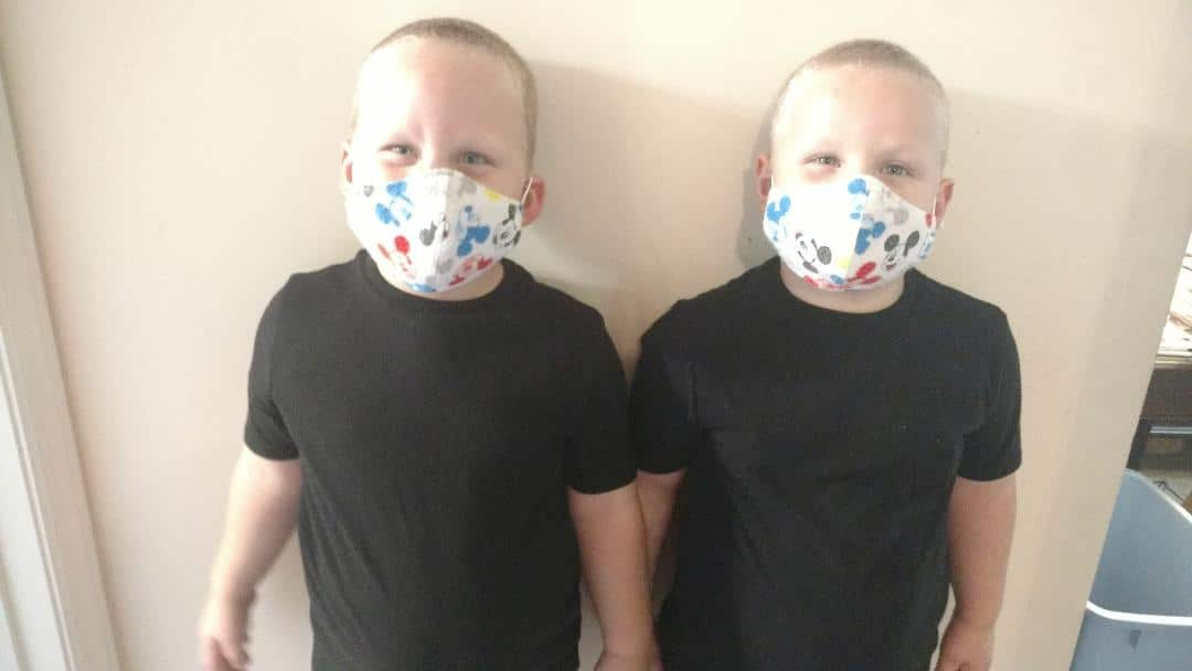 four years old twin boys in masks