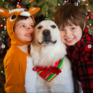 Two small kids with family dog at Christmas