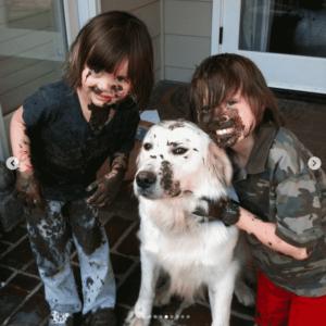two muddy kids and one muddy white dog
